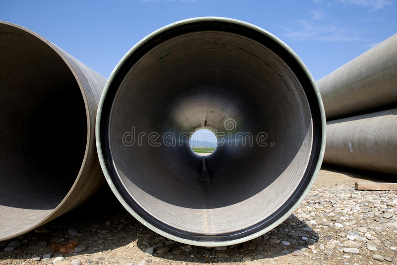 Long large pipe. Stacked beside highway for construction stock photo