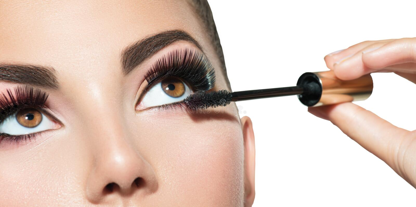 Long lashes closeup. Beautiful woman applying mascara on her eyes royalty free stock photos