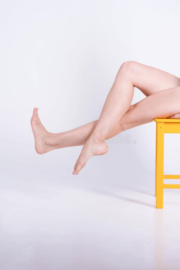 Long legs woman is sitting on a white background. Depilation stock photos