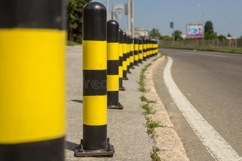 Long line of yellow and black traffic signs to deter the cars around the road.  stock images