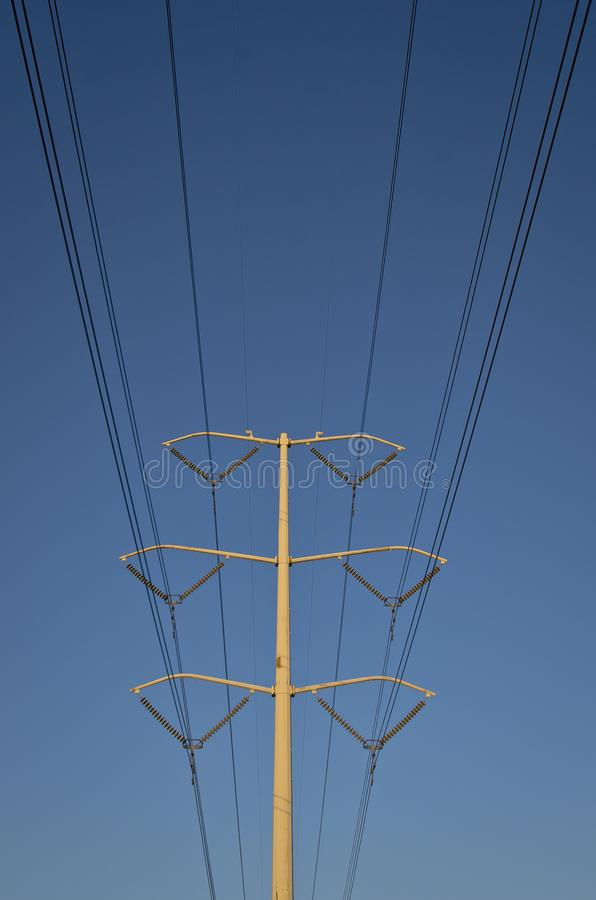 The long lone solo power cable line sin the blue sky. The big long cables on the power pole in the summer sun up in the blue sky royalty free stock image