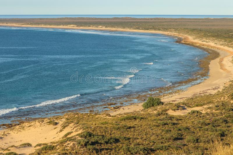 Long and lonely beach in Ningaloo. Curved bay with long beach and only a few people at waters edge. Ningaloo Australia stock images