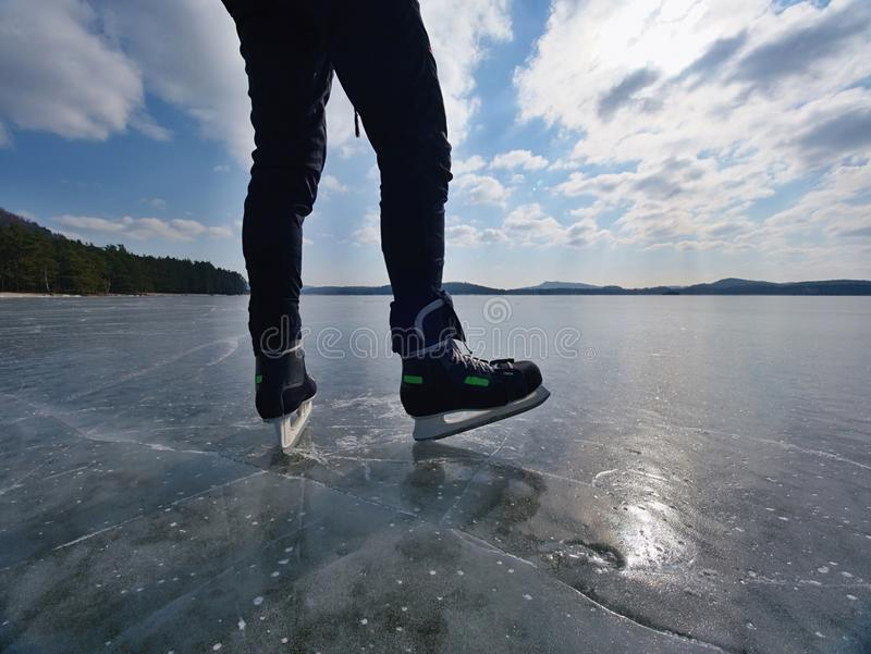 Long male legs in black leggins with hockey skates. Outdoor ice skating. On the lake royalty free stock photos