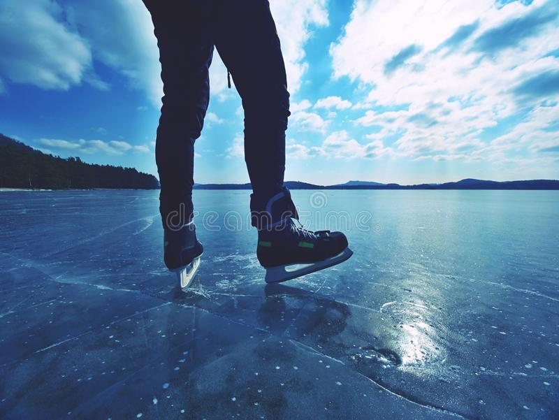 Long male legs in black leggins with hockey skates. Outdoor ice skating. On the lake stock photos