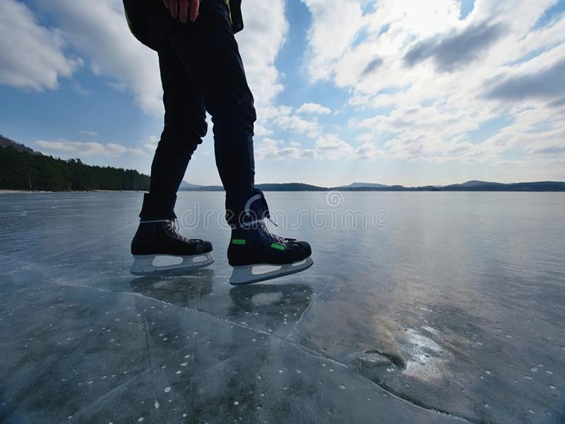 Long male legs in black leggins with hockey skates. Outdoor ice skating. On the lake stock photography