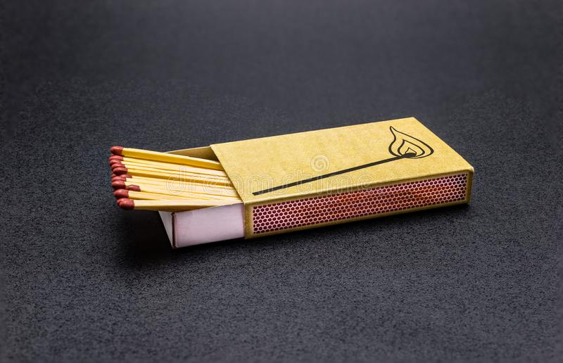 Long matches lying in a matchbox on a black background, with a clipping path. royalty free stock photo
