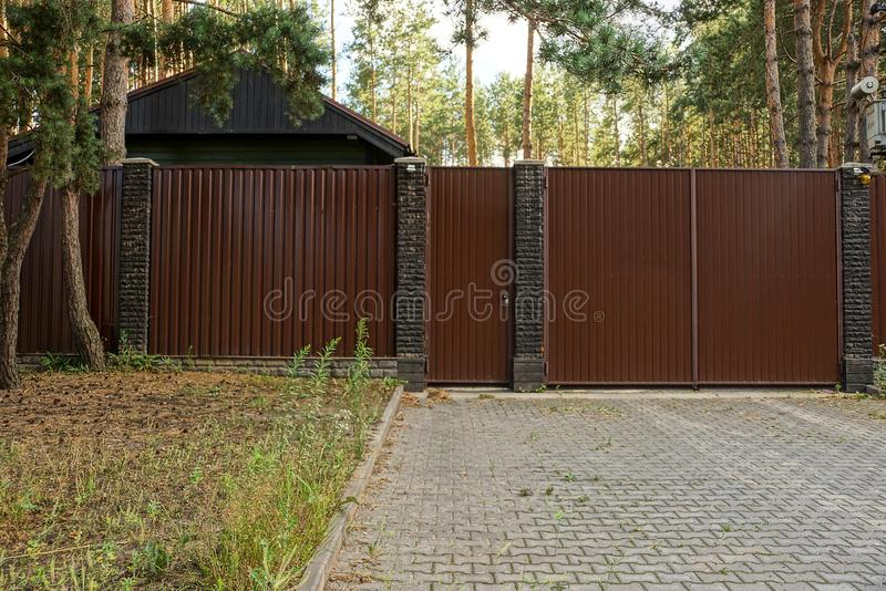 Long metal brown fence and gate at the sidewalk and grass outside royalty free stock photography