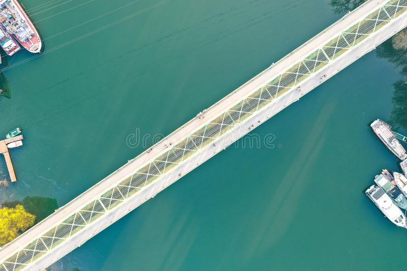 Long narrow bridge going over a large river with ships docked at the coast royalty free stock photo