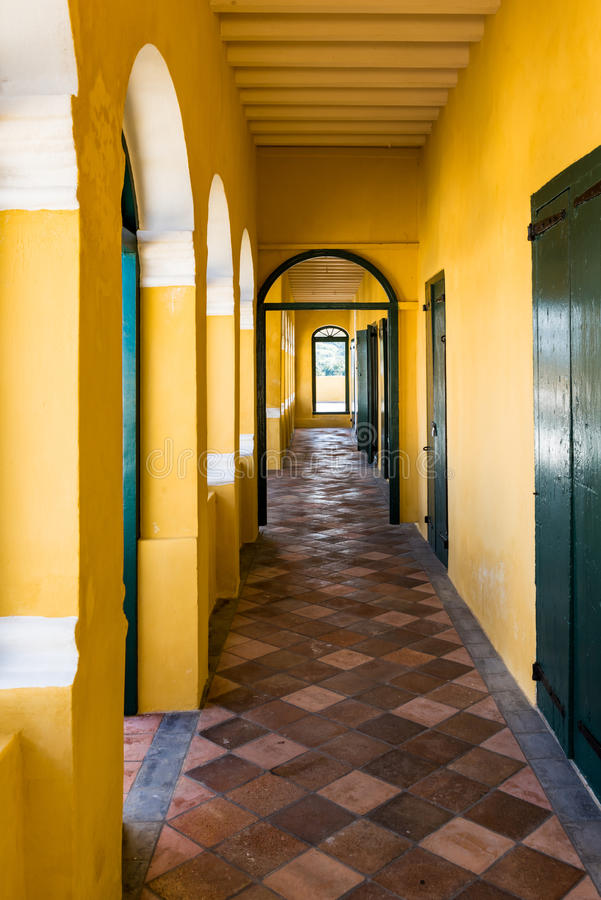 Long narrow passageway in old fort with yellow walls and brown c. Heckered floor. Arched window at the end royalty free stock photography