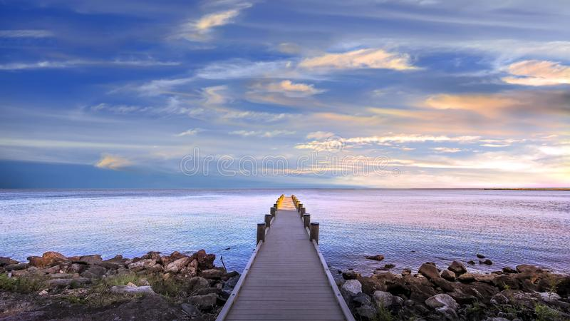 Long narrow pier protruding out into Chesapeake Bay at sunset under a magnificent sky stock photo