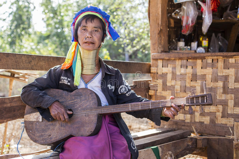 Long-Neck Woman, Myanmar. Loikaw, Myanmar-January 23, 2016. A portrait of a woman from the Padaung tribe (Karen) playing a guitar. The ladies are famous for royalty free stock image