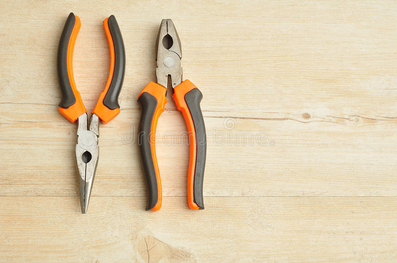 A long nose pliers and a pliers. Isolated on a wooden background royalty free stock images