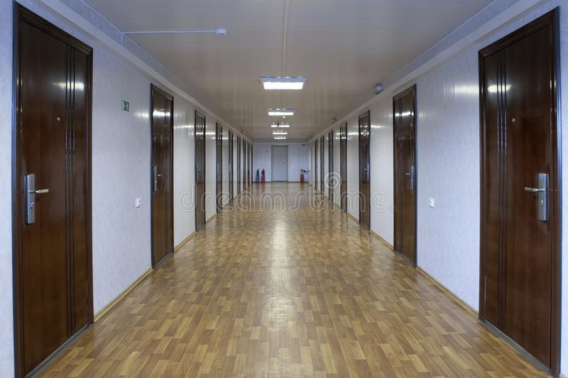 Long office hallway with many doors of dark red wood. Empty office corridor with many doors of dark red wood stock images