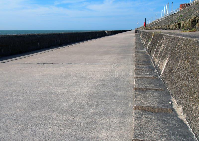 Long passage couvert piétonnier concret le long de la digue dans le lancashire de Blackpool avec le soleil et la mer d'été photos libres de droits