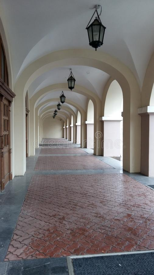 A long passage under the arches with tiled floor and lanterns on the ceiling stock photo