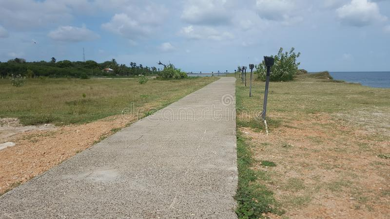 Long path by the beach. A long winding promenade at the KKS beach, in Jaffna stock image