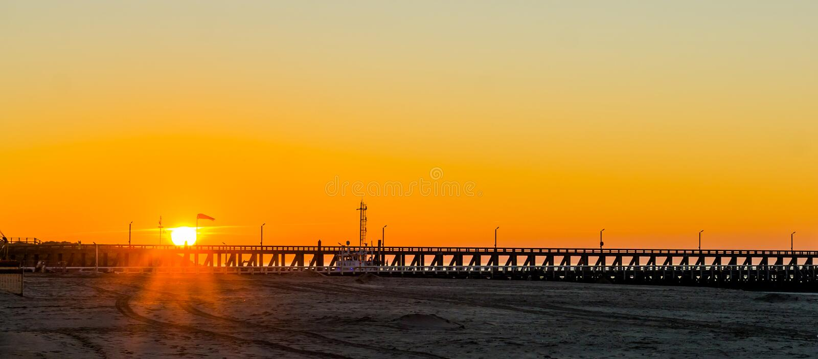 Long pier at sunset on the beach of Blankenberge, Belgium, sunset with a colorful sky. A long pier at sunset on the beach of Blankenberge, Belgium, sunset with a stock photos