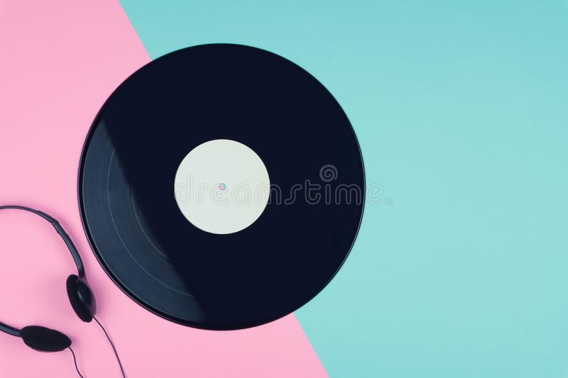 A long play vinyl record or LP with a black on-ear headphone stock photography