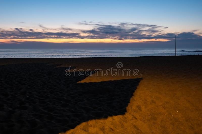 Long, pointy shadows cast by wooden beach huts on sand at sunset. With beautiful colors in sky stock photos