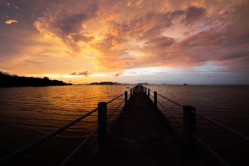Long pont au-dessus de la mer avec le beau coucher du soleil derrière de petites montagnes photographie stock libre de droits