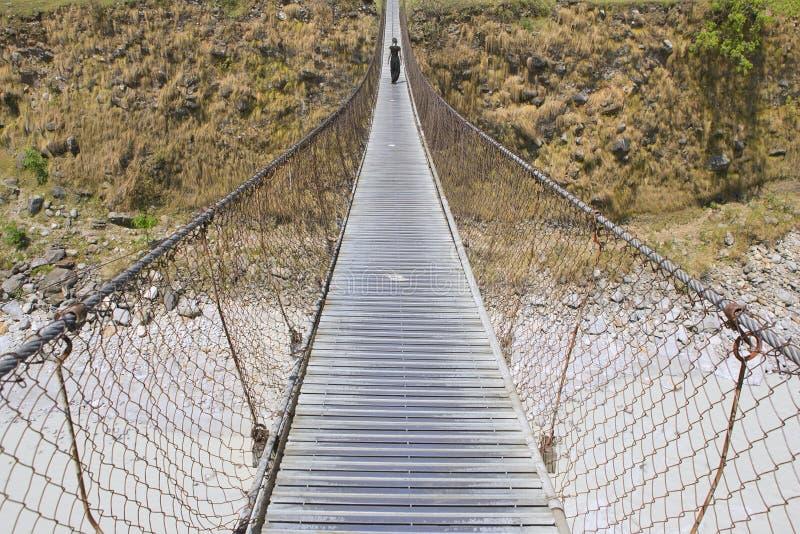 Long pont de pied avec la femme de marche, pont au-dessus de rivière de montagne, images stock