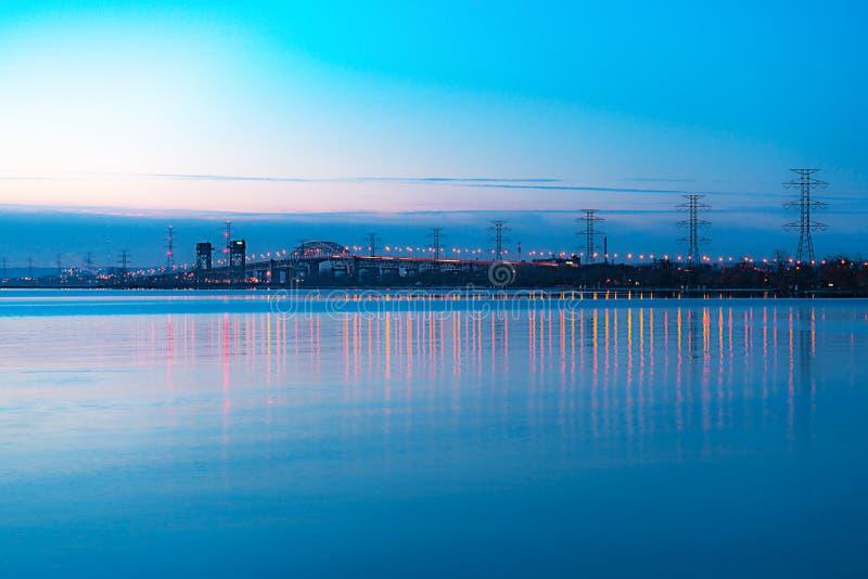 Long pont skyway et d'ascenseur embrasé avec des lumières se reflétant dans le bleu photos stock