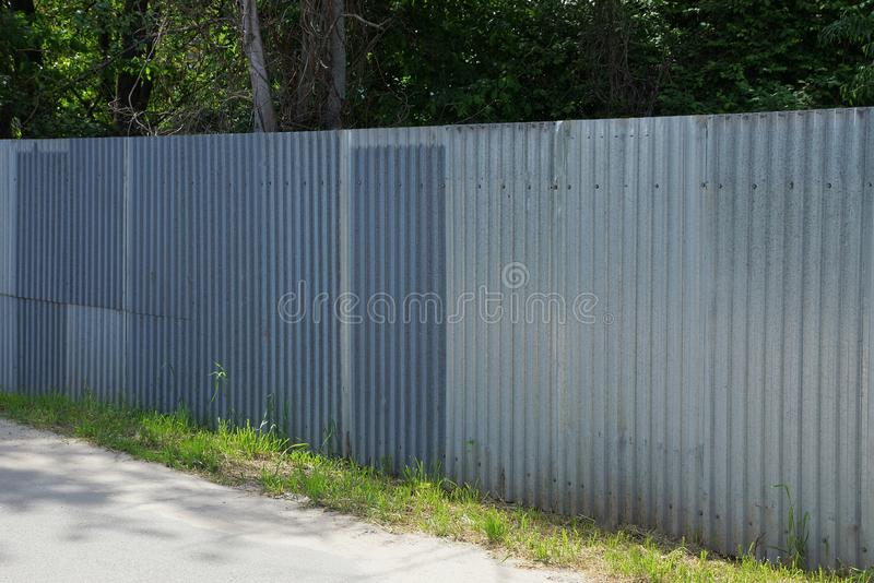 Long private gray metal fence outside stock photos