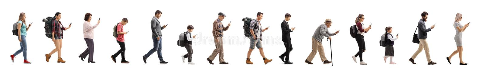 Long queue of people walking and using a mobile phone royalty free stock photo