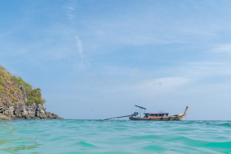 Long range shot an old wooden oriental ship close to an island with blue sky in the background stock photo