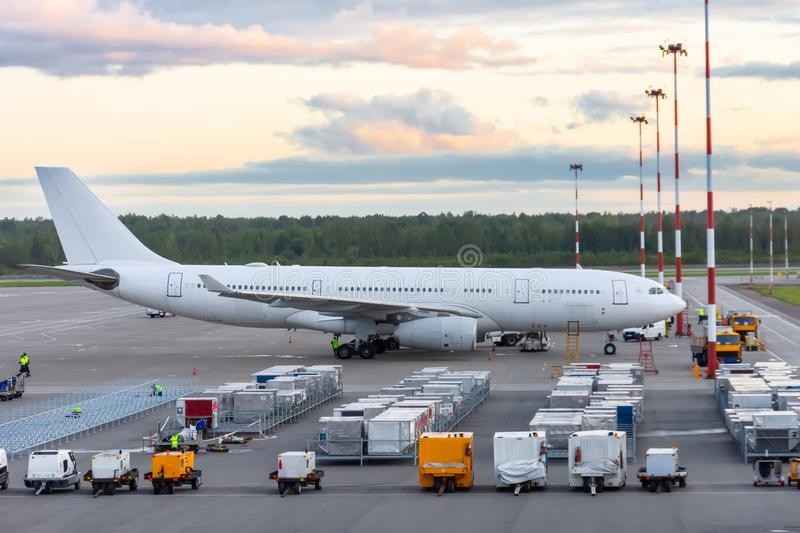 Long-range wide-body aircraft parked at the airport, in front of it is a food containers and mobile power supplies. Flight service stock photography
