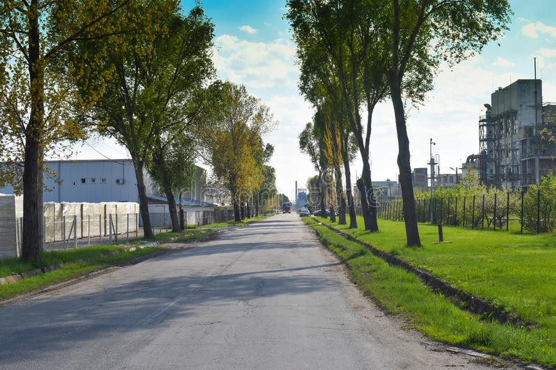 Long road in the industrial area near the chemical plant. The nature is trying to resist there royalty free stock images