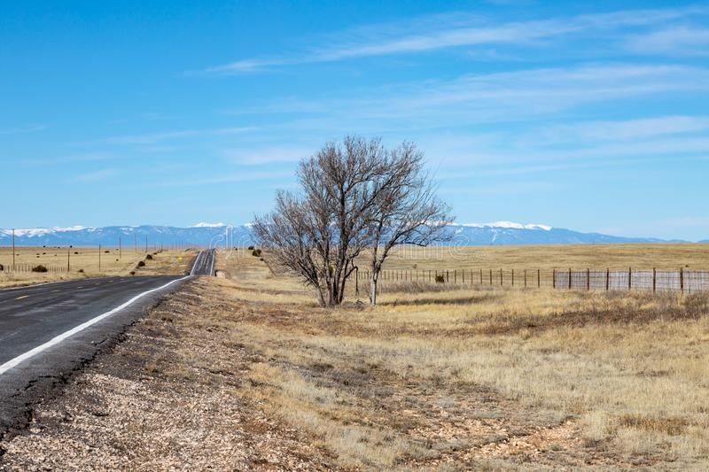 A New Mexico Winter Landscape. A long road in New Mexico, with snow capped mountains in the distance stock images