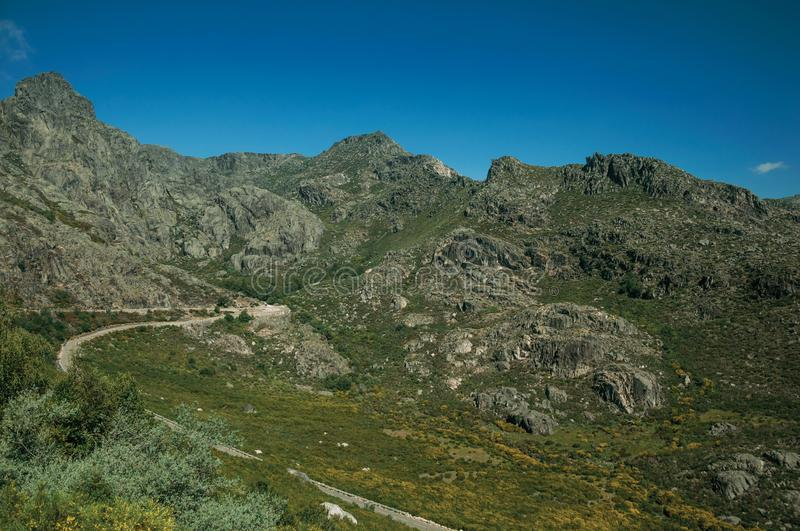 Long roadway passing through rocky landscape. With green bushes in a sunny day, at the highlands of Serra da Estrela. The highest mountain range in continental stock images