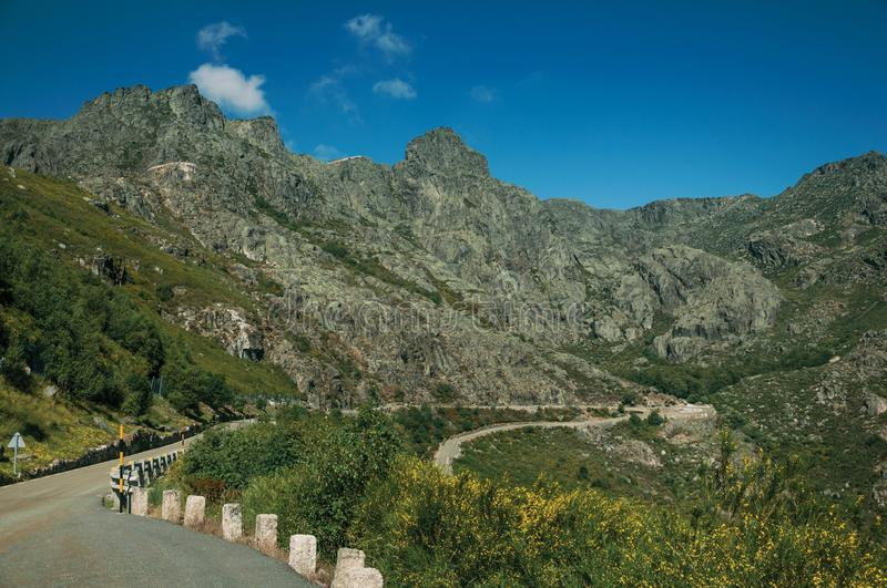 Long roadway passing through rocky landscape. With green bushes in a sunny day, at the highlands of Serra da Estrela. The highest mountain range in continental royalty free stock image