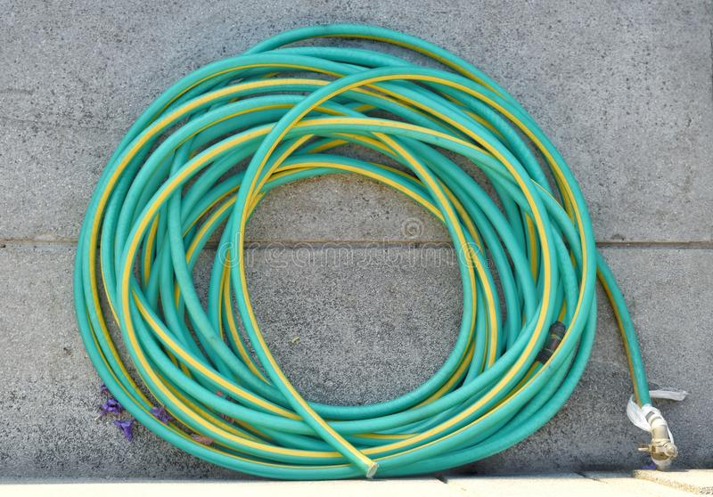 A long roll of green-yellow rubber tube used for watering trees and flower stock image