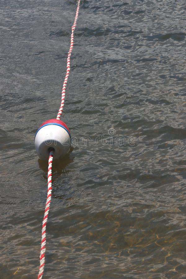 Red, white and blue buoy with red and white rope. Long rope with small buoys mark the safe swimming area at Pine Mountain Lake, California stock photos