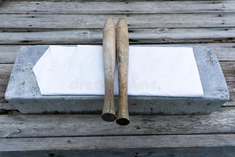 Long, round wooden bat use for beat cloths called `pangmangi` and flat stone use for lay the cloths called `tatumi-tol` stock photo