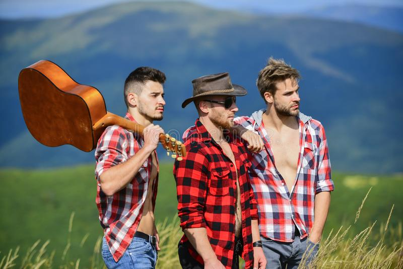 Long route. Adventurers squad. Tourists hiking concept. Hiking with friends. Men with guitar hiking on sunny day. Group. Of young people in checkered shirts royalty free stock photography
