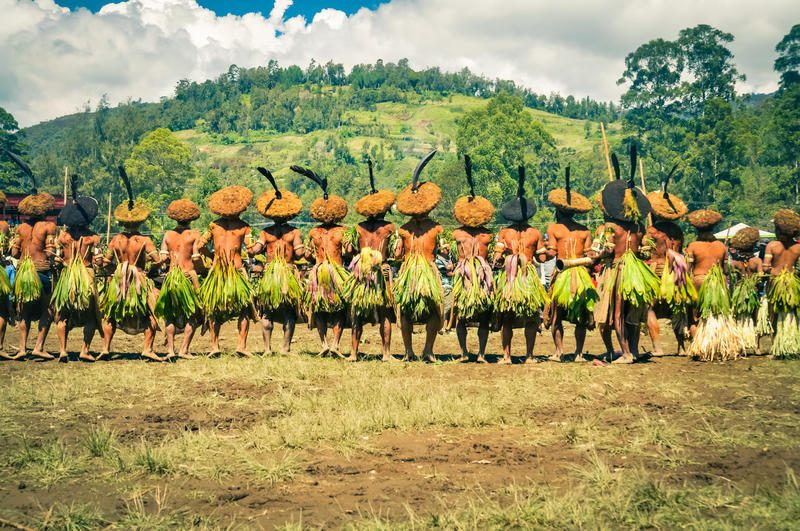 Long row of men in Papua New Guinea. Wabag, Papua New Guinea - circa August 2015: Native half-naked men during traditional Enga cultural show in Wabag, Papua New royalty free stock image