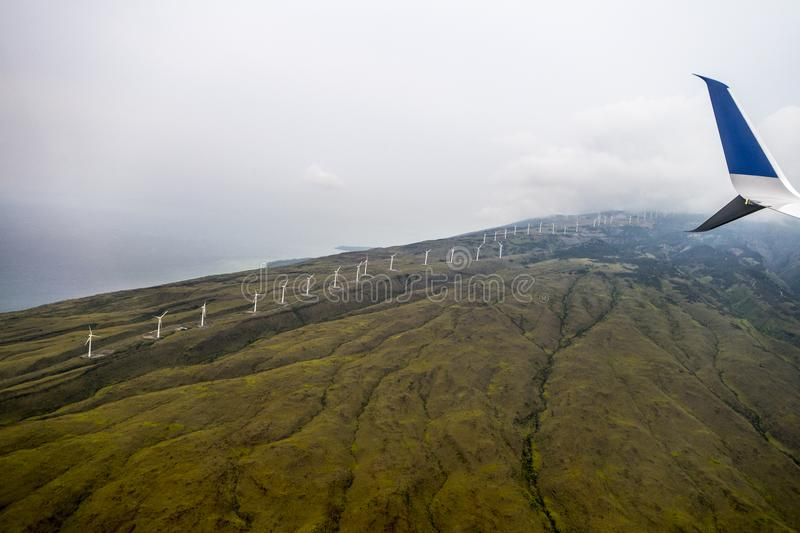 high mountain elevation angle view for plane, line of wind tutbines in a row on stock photos