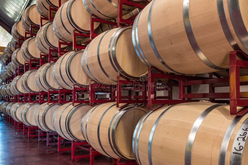 Long Row of Wine Barrels on Rack. Vineyards inventory of wine barrels stacked on red metal racks royalty free stock image