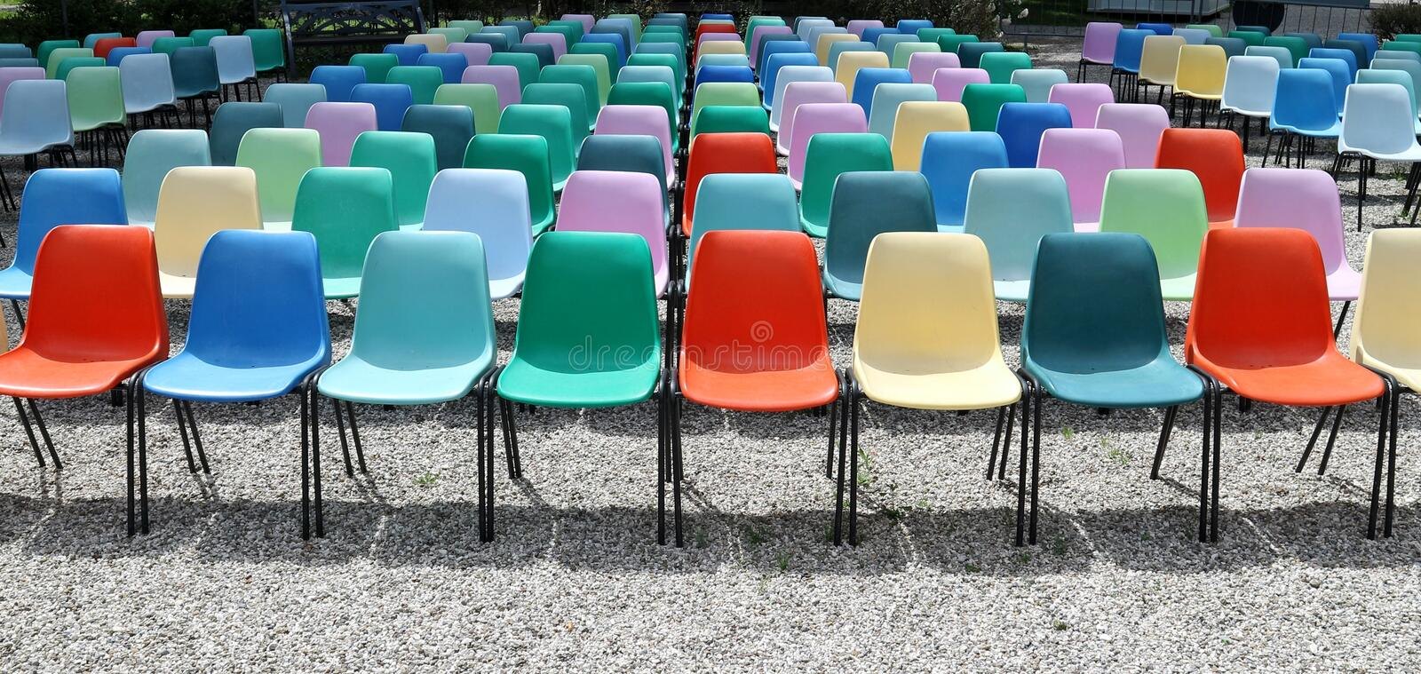 Long rows of empty colorful plastic chairs geometrically arranged under the sun. Texture and background. Copy space royalty free stock images