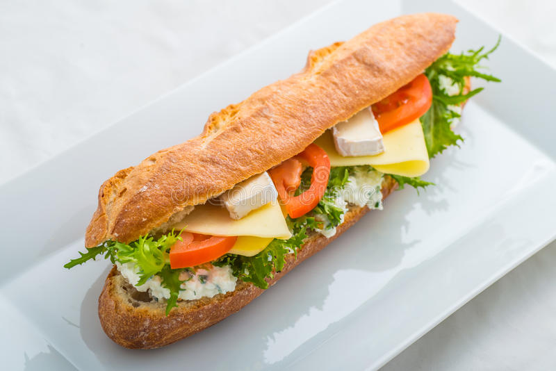 Long sandwich with tofu, cheese, tomatoes and lettuce. Isolated on white background, product photography for restaurant stock photo