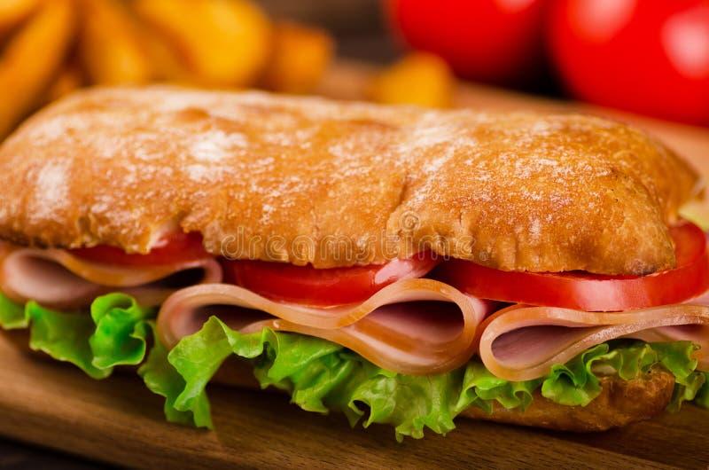 Long sandwiche avec des tranches de tomates et de jambon frais images stock