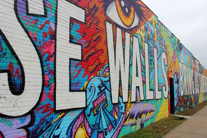 Gorgeous graffiti in bright colors painted on long brick wall with words of inspiration, Austin, Texas, 2018. Long section of old brick wall painted in bright stock photography