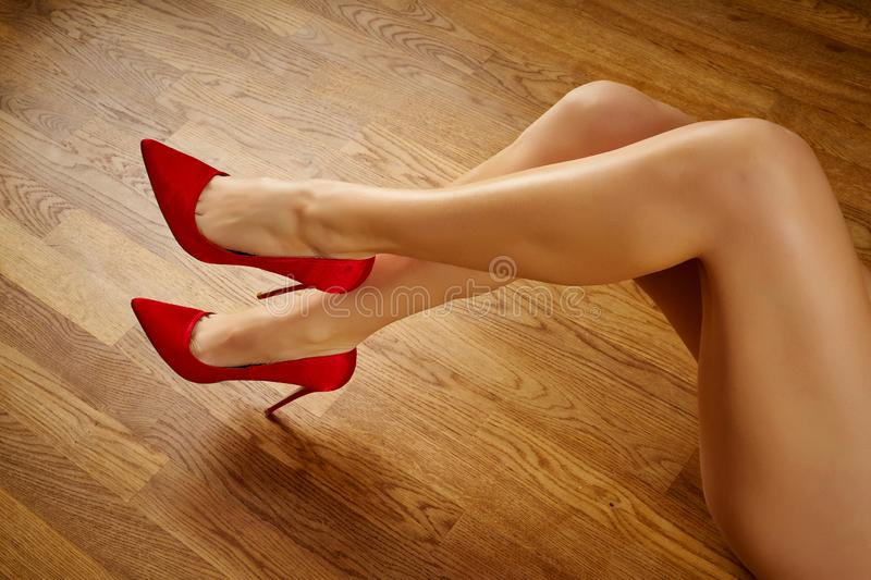 Long woman`s legs in red high heels on wooden floor. Long woman`s legs in red high heels on wooden oak floor stock image