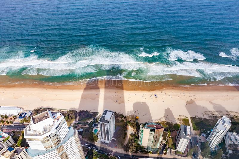 Long shadows on the beach from skyscrapers. Long shadows on the beach from skyscrapers with people bathing - birds eye view. Gold Coast, QLD, Australia royalty free stock photography
