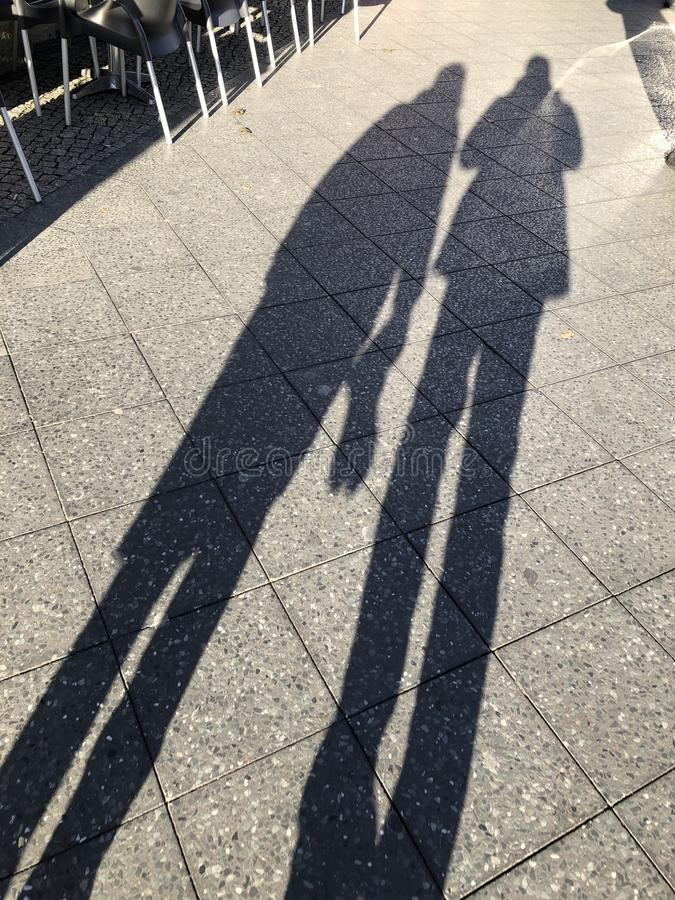 Long shadows of two people on the sidewalk stock photos