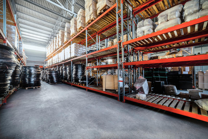 Long shelves with a variety of boxes and containers. Warehouse industrial goods. Large long racks. Cardboard boxes and coiled plastic tube. Toning the image royalty free stock photography