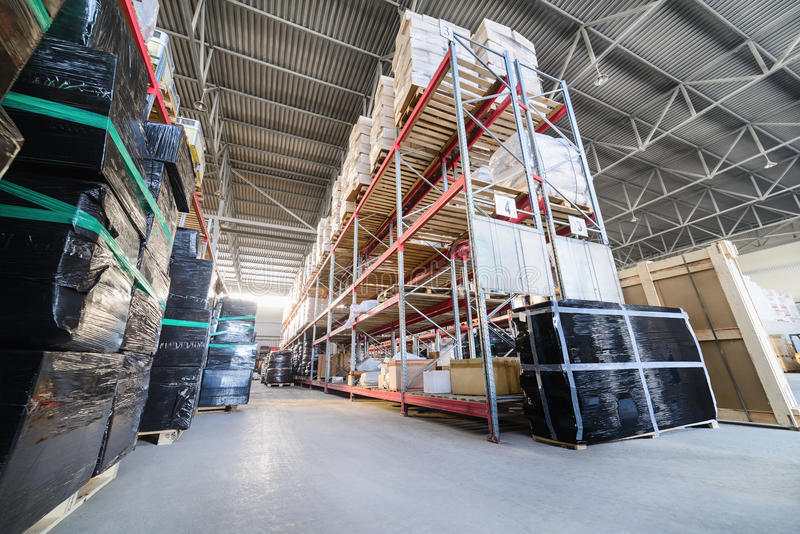 Long shelves with a variety of boxes and containers. Warehouse industrial goods. Large long racks. Cardboard boxes and coiled plastic tube. Toning the image stock images